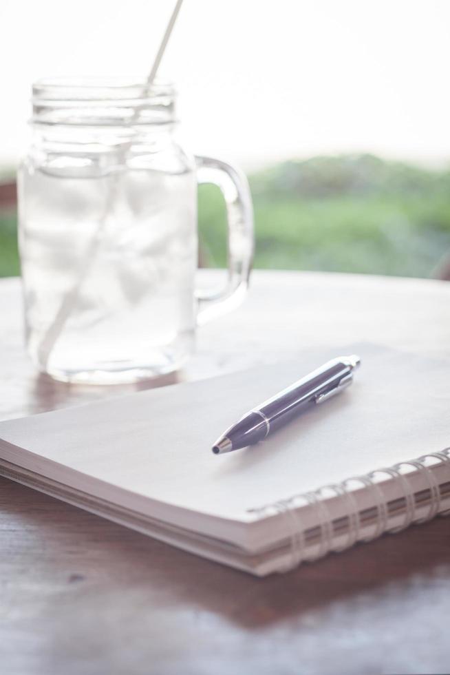 arbetsstation med anteckningsbok och penna foto