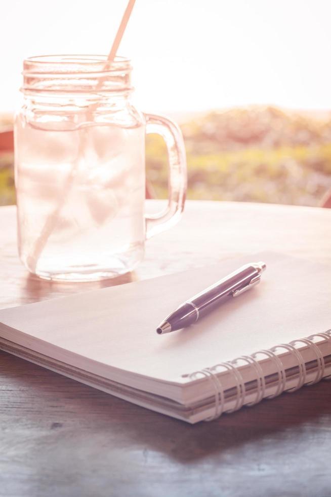 anteckningsbok med en penna och en burk vatten foto