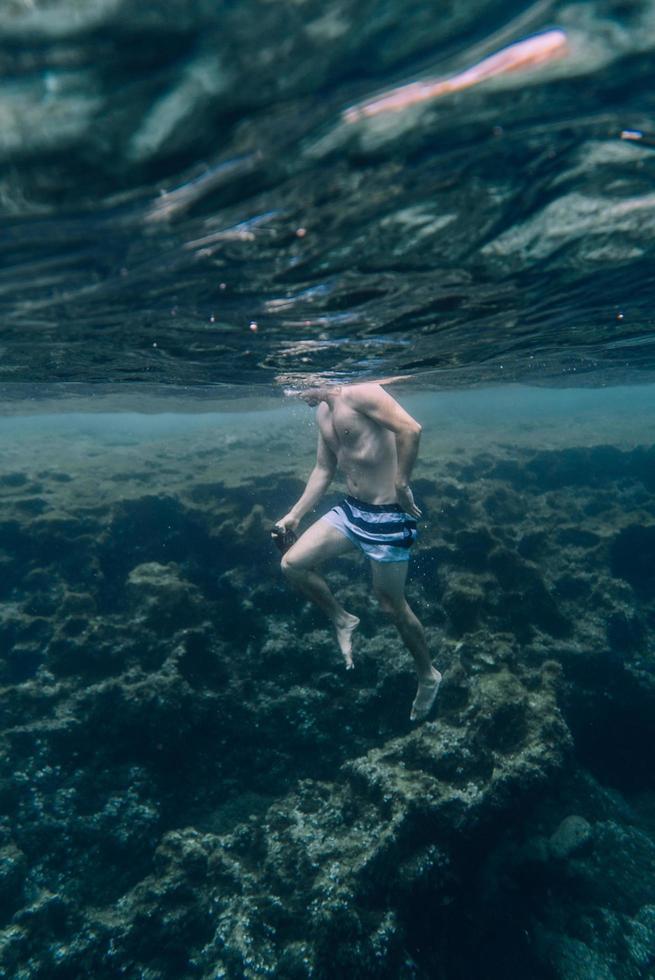 man simmar under vattnet foto