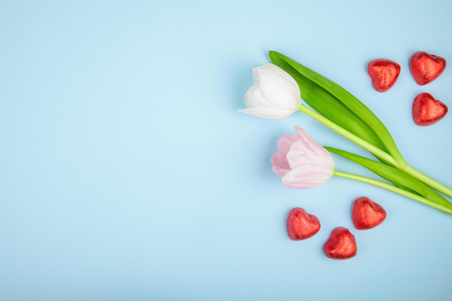 tulpaner och hjärtformade choklad på en blå bakgrund foto