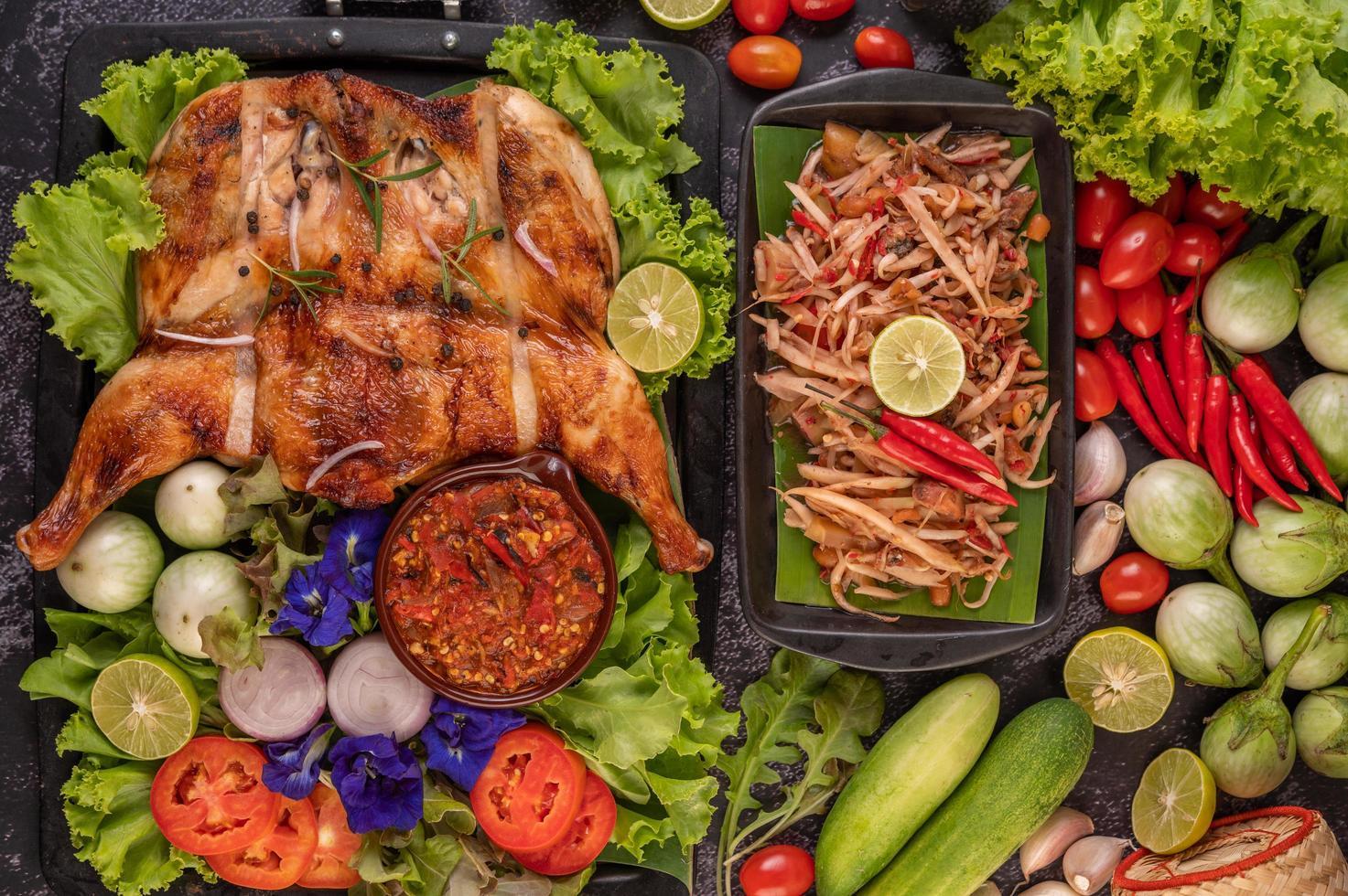 thailändsk papayasallad omgiven av grönsaker och kyckling foto