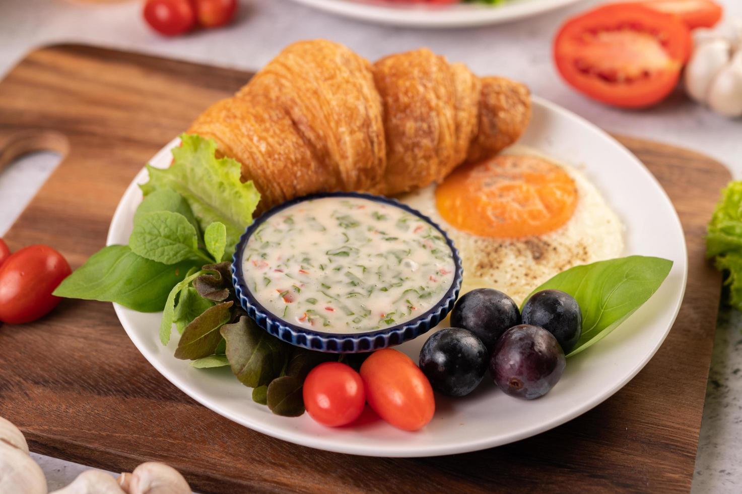 croissant, stekt ägg, salladsdressing, svarta druvor och tomater foto