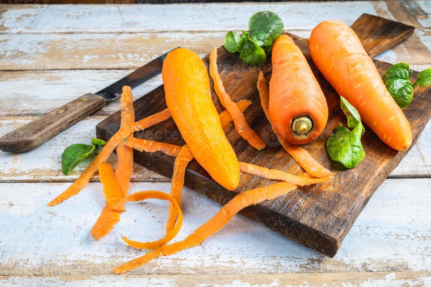 morötter på en skärbräda foto