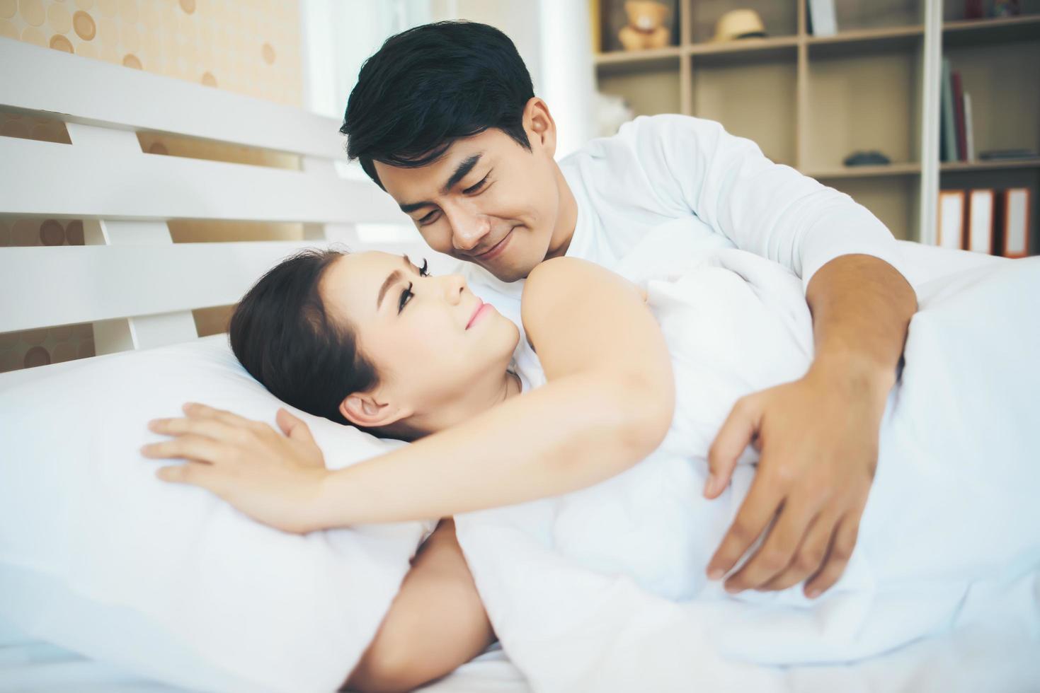 lyckliga par som lägger ihop i deras säng foto