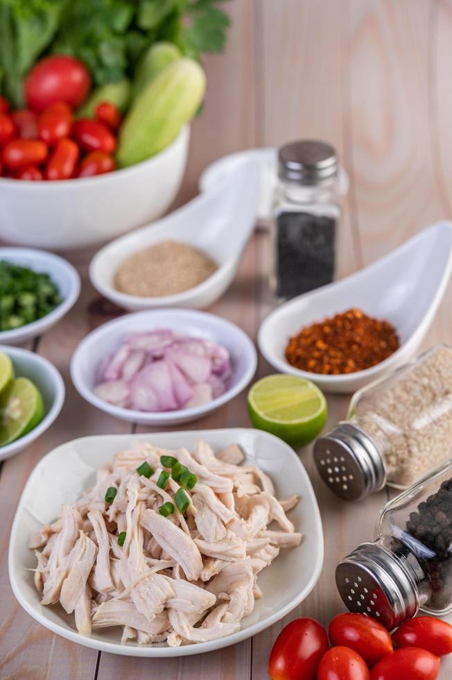 kokta kycklingbitar med grönsaker och kryddor på ett träbord foto