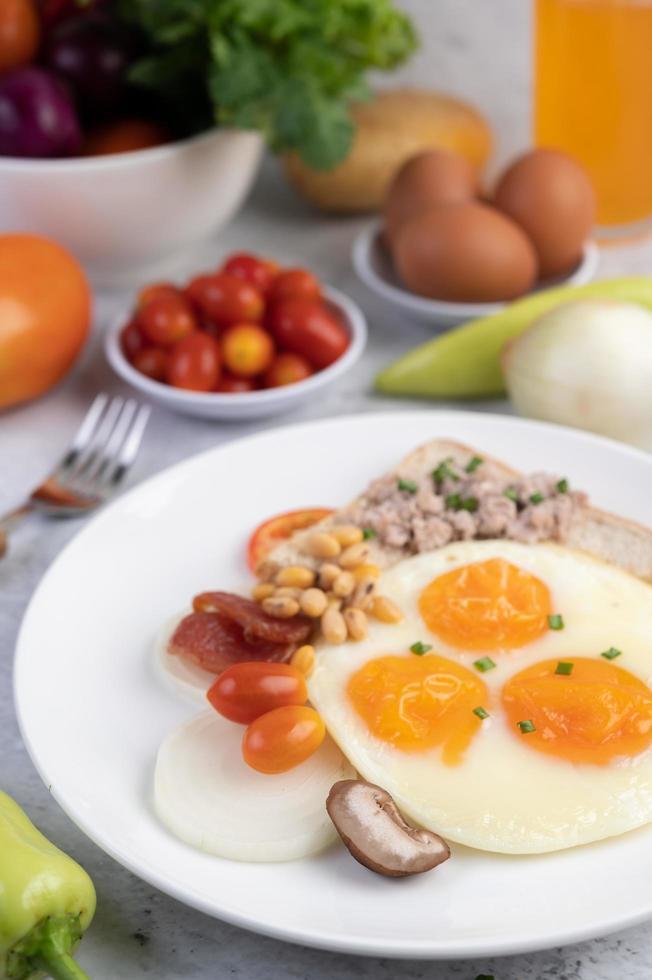 stekt ägg, korv, malet fläsk, bröd och röda bönor foto