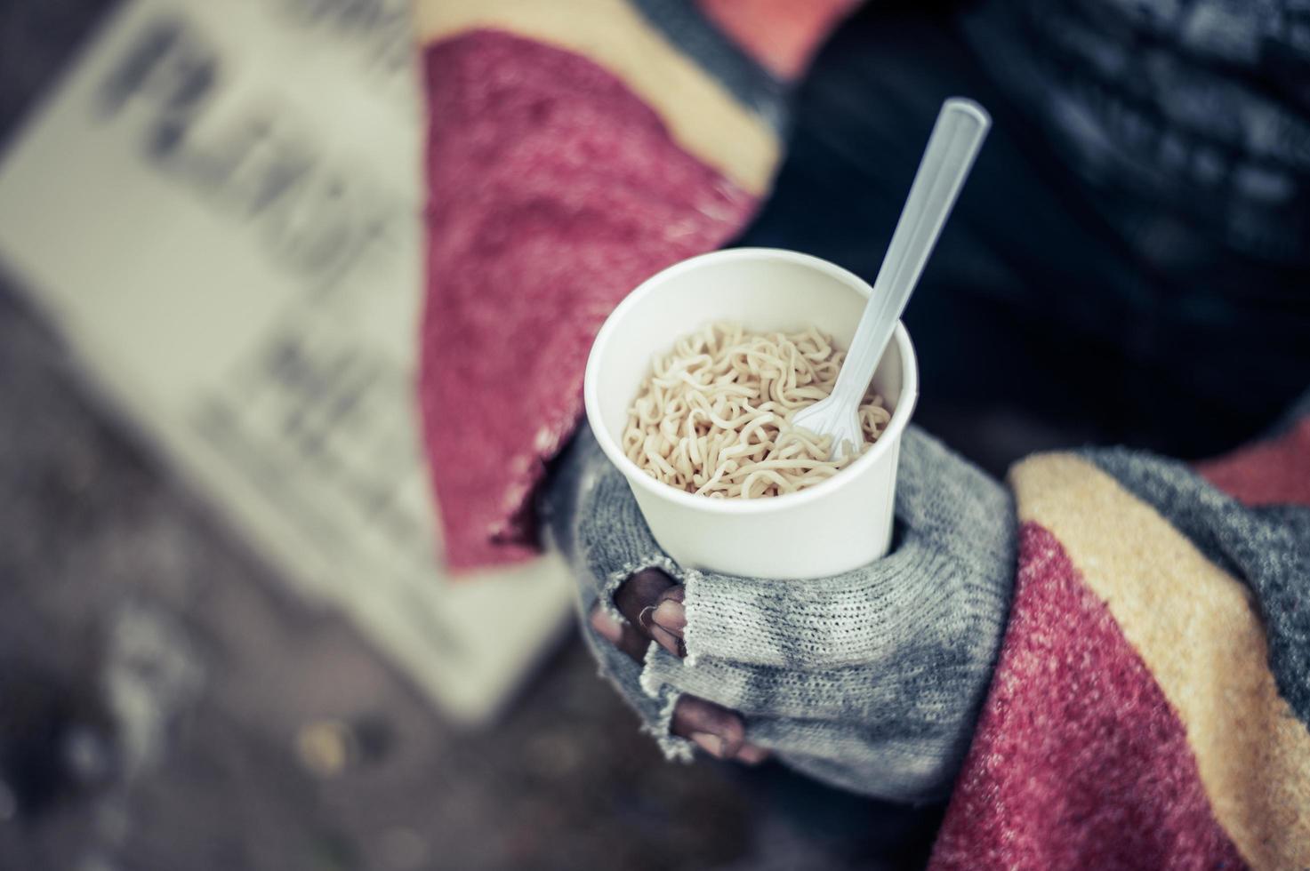 personen sitter insvept i tyg och äter nudlar foto