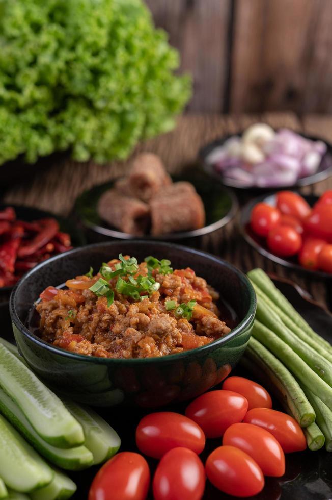 söt fläskskål med gurkor, långa bönor och tomater foto