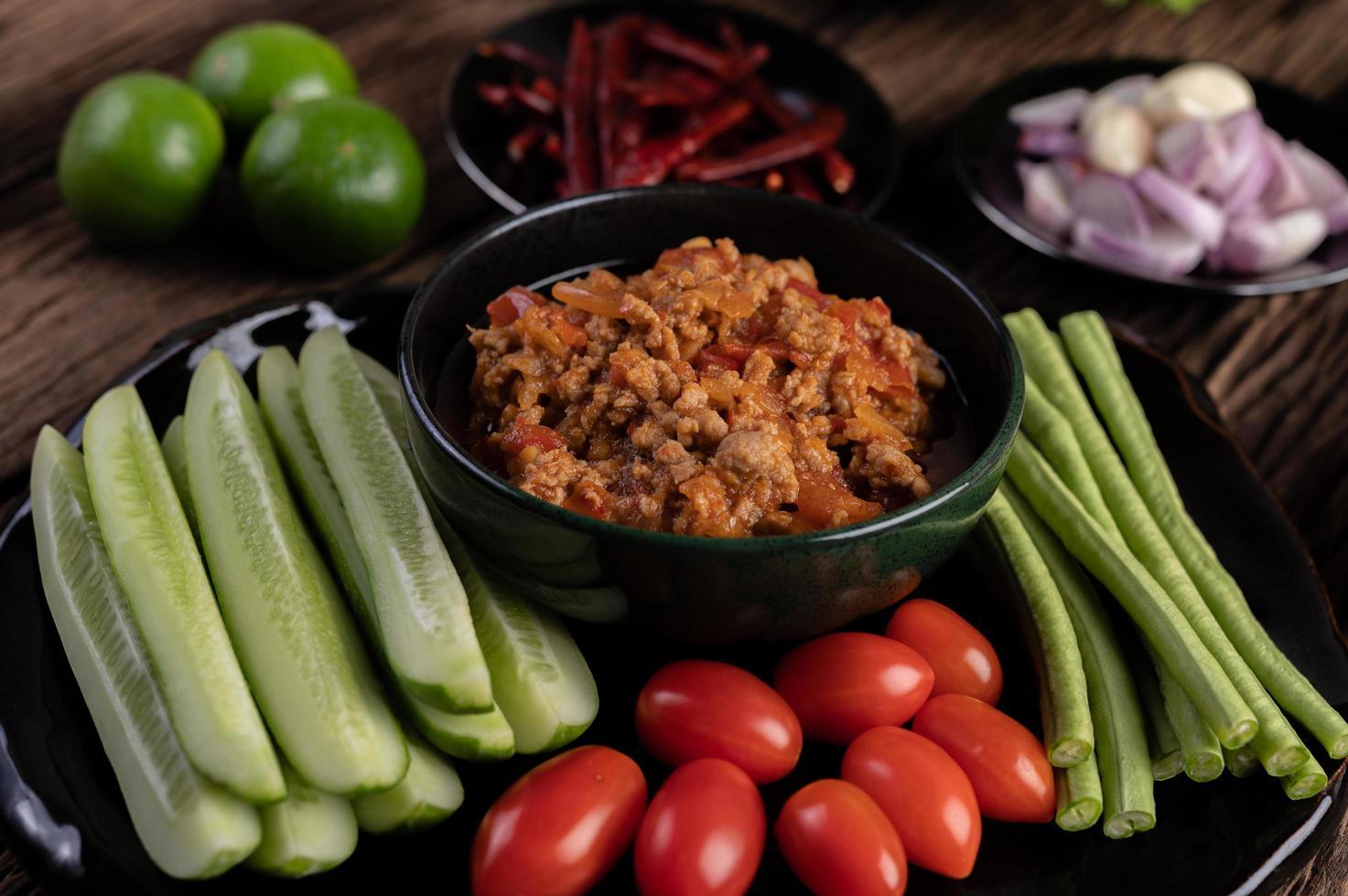 sött fläsk med gurkor, långa bönor, tomater och sidrätter foto