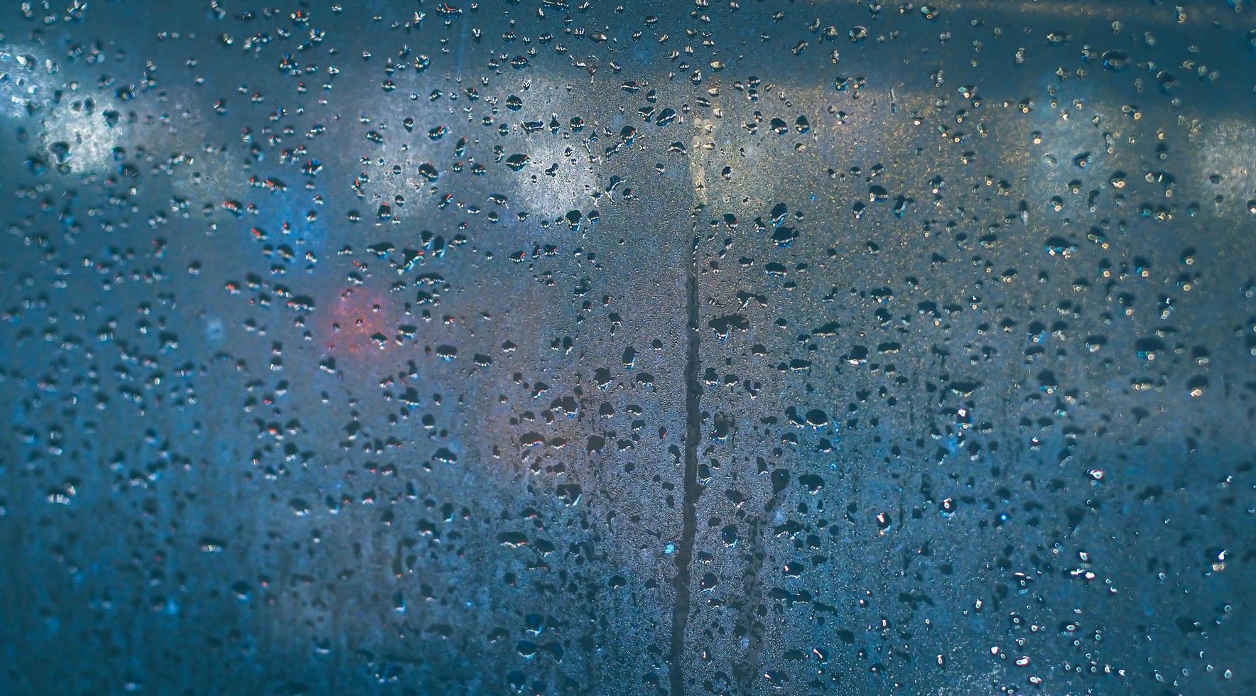 regndroppar på bilens fönster. abstrakt oskärpa bokeh av trafik och bil ljus. foto