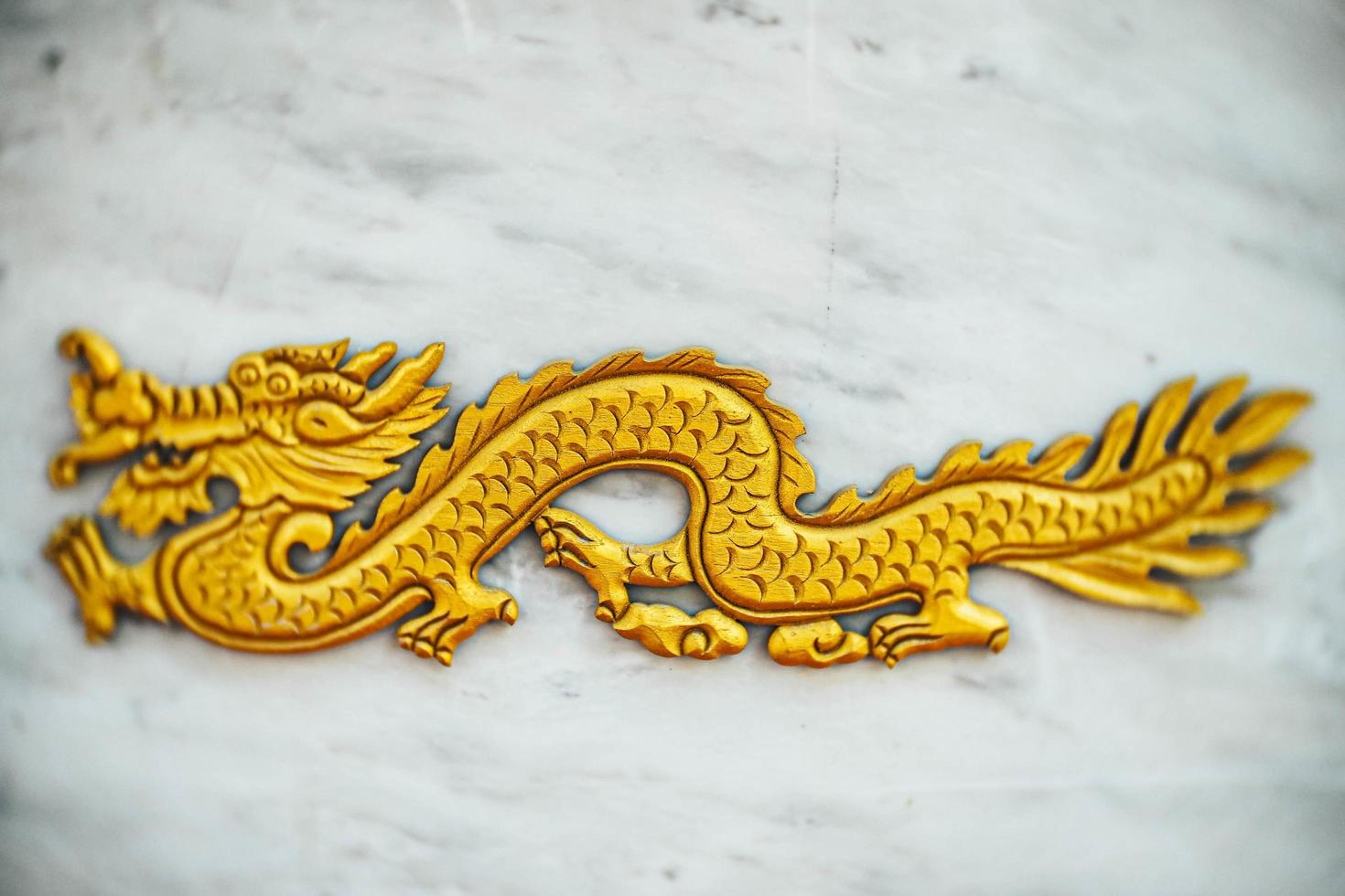 selektiv inriktning kinesisk drake, gyllene drake, gulddrake på marmorbakgrund foto