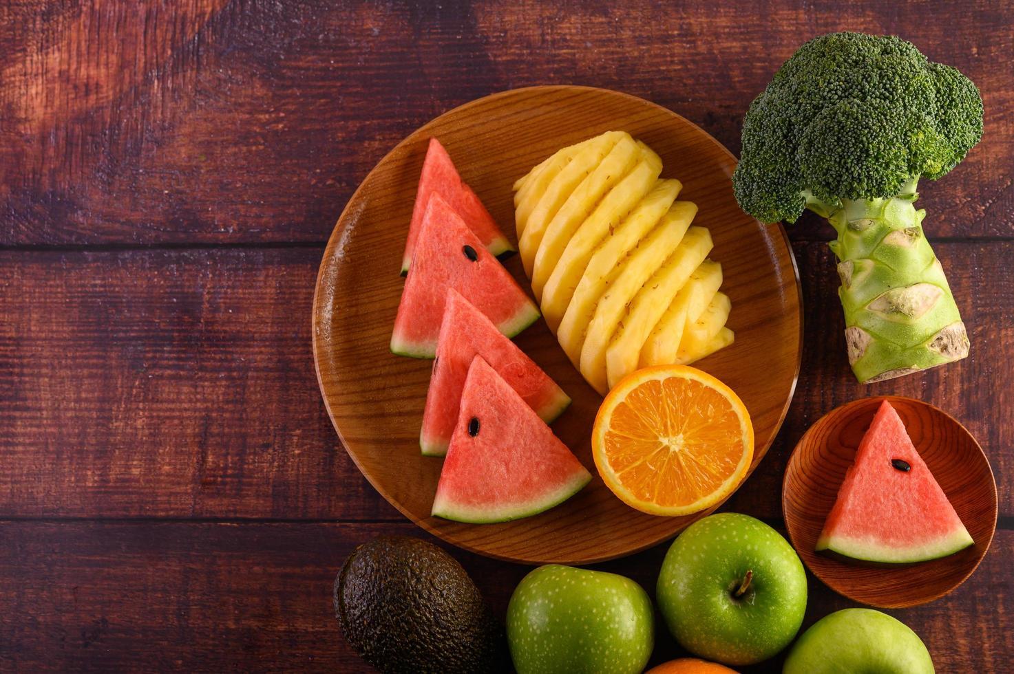färgrik vattenmelon, ananas, apelsiner med avokado och äpplen foto