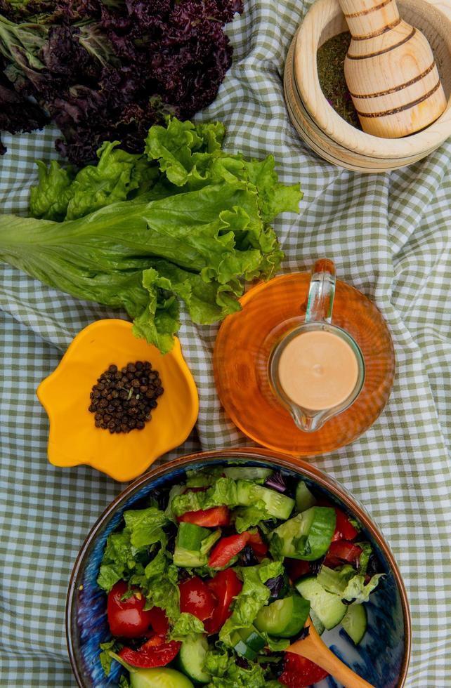 ovanifrån av grönsaksallad med sallad basilika svartpeppar vitlök kross smält smör på rutigt tyg bakgrund foto