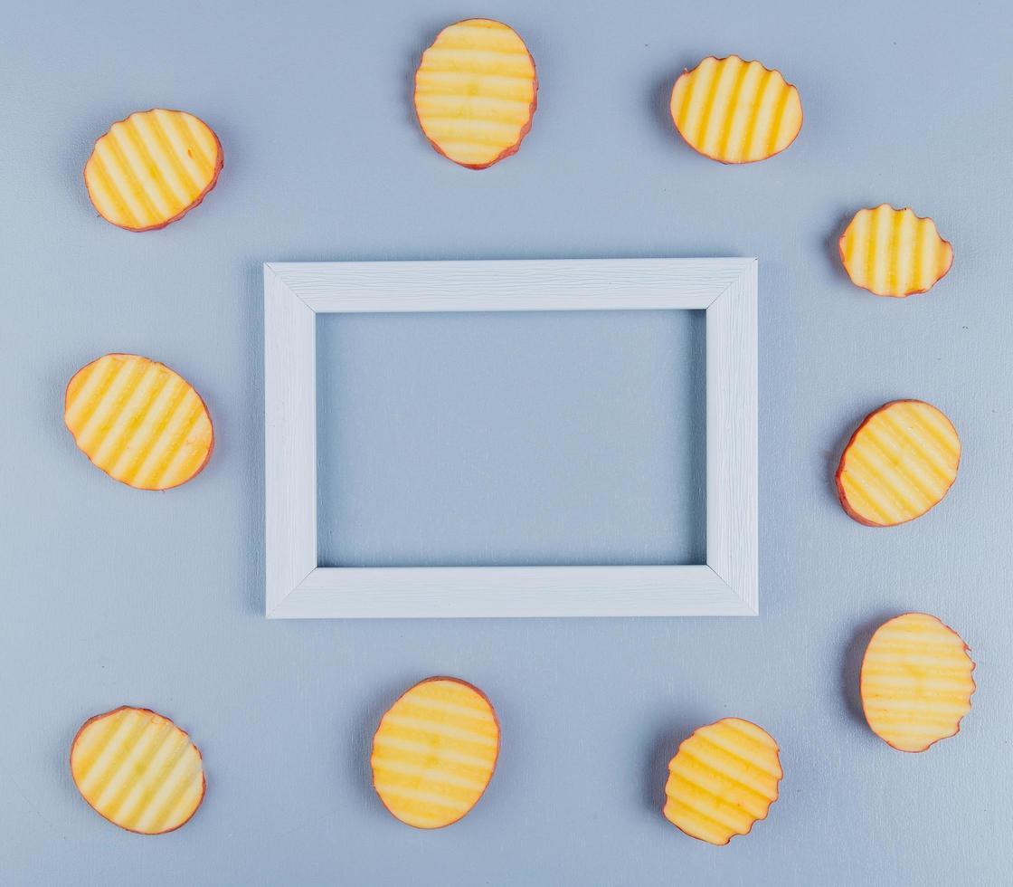 ovanifrån av potatisskivor runt ramen på blå bakgrund med kopieringsutrymme foto