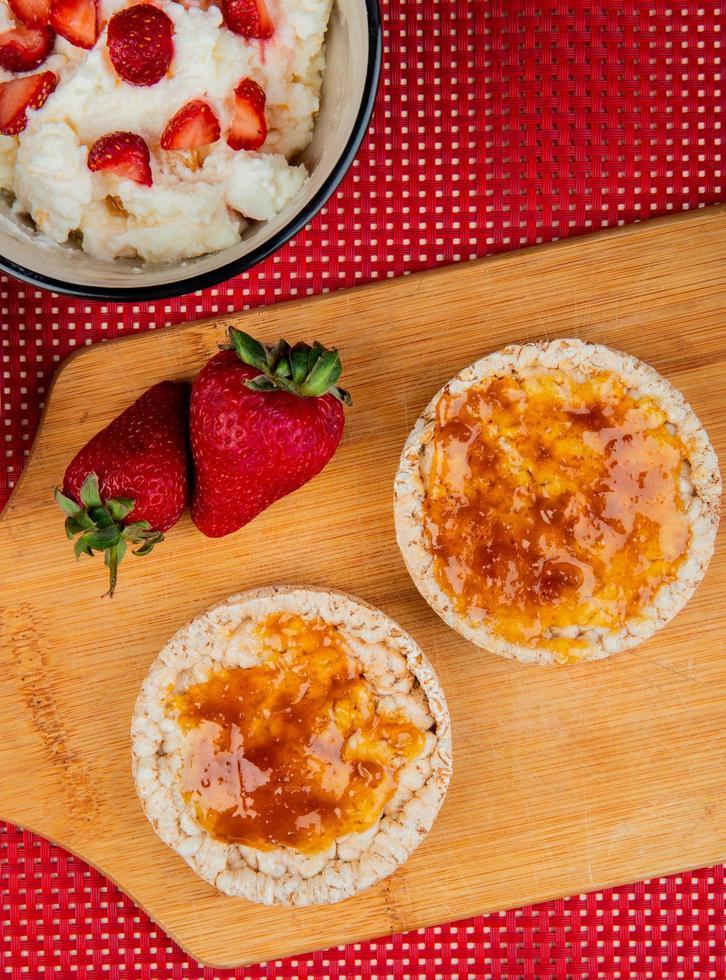 ovanifrån av krispiga knäckebröd smorda med sylt och jordgubbar på skärbräda med havregryn på röd och vit bakgrund foto