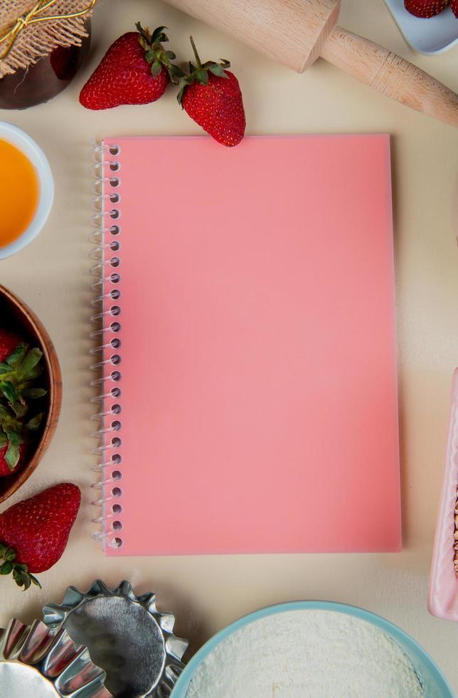 ovanifrån av anteckningsblock med jordgubbar smör mjöl runt på vit bakgrund med kopia utrymme foto