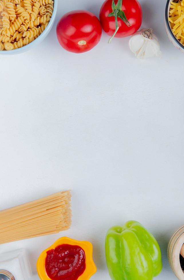 ovanifrån av makaroner som rotini och vermicelli med tomater ketchup vitlökspeppar salt på vit bakgrund med kopia utrymme foto