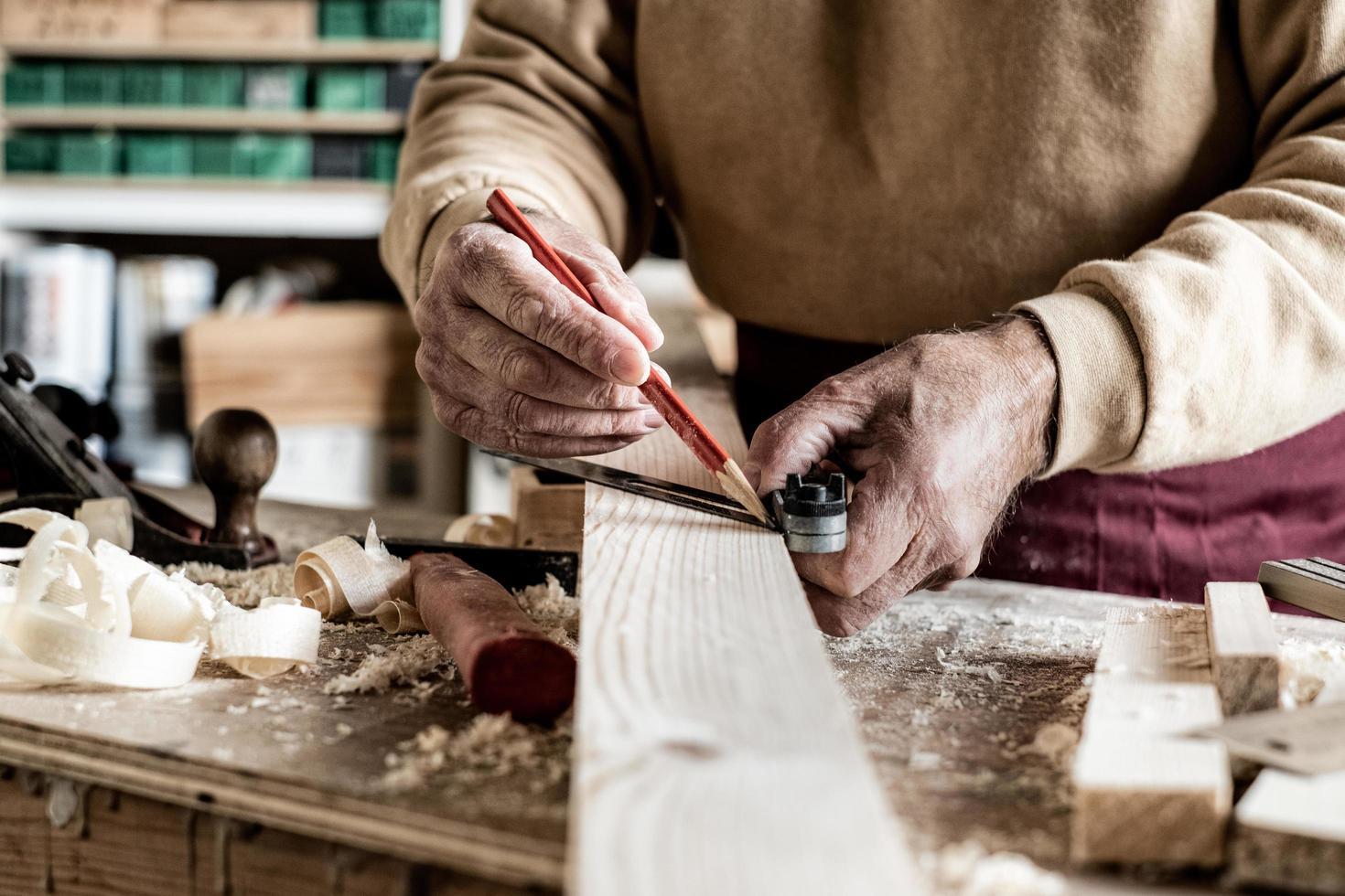 snickare som gör mått med en penna och en metalllinjal på träplanka foto