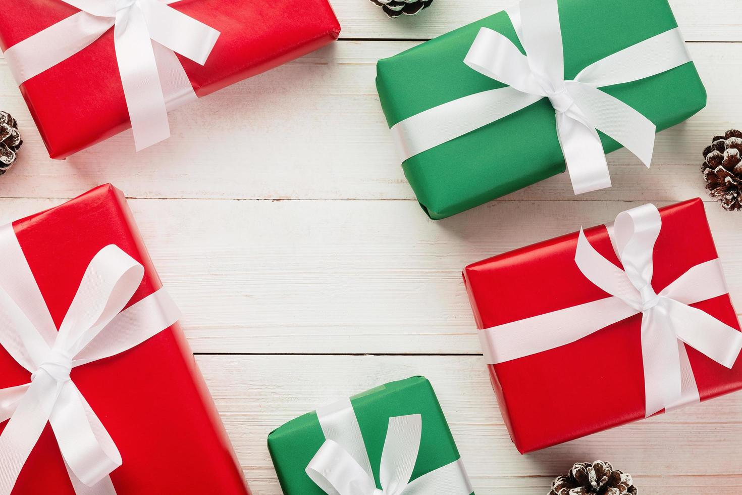 jul och nyår med presentaskar och snö kotte dekoration på vit träbord bakgrund ovanifrån med kopia utrymme foto