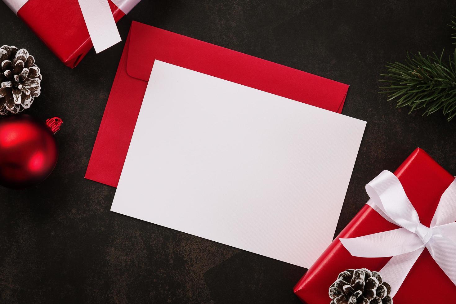 tomt vitt gratulationskort och kuvertmodell med julklappsdekorationer på grungebakgrund foto