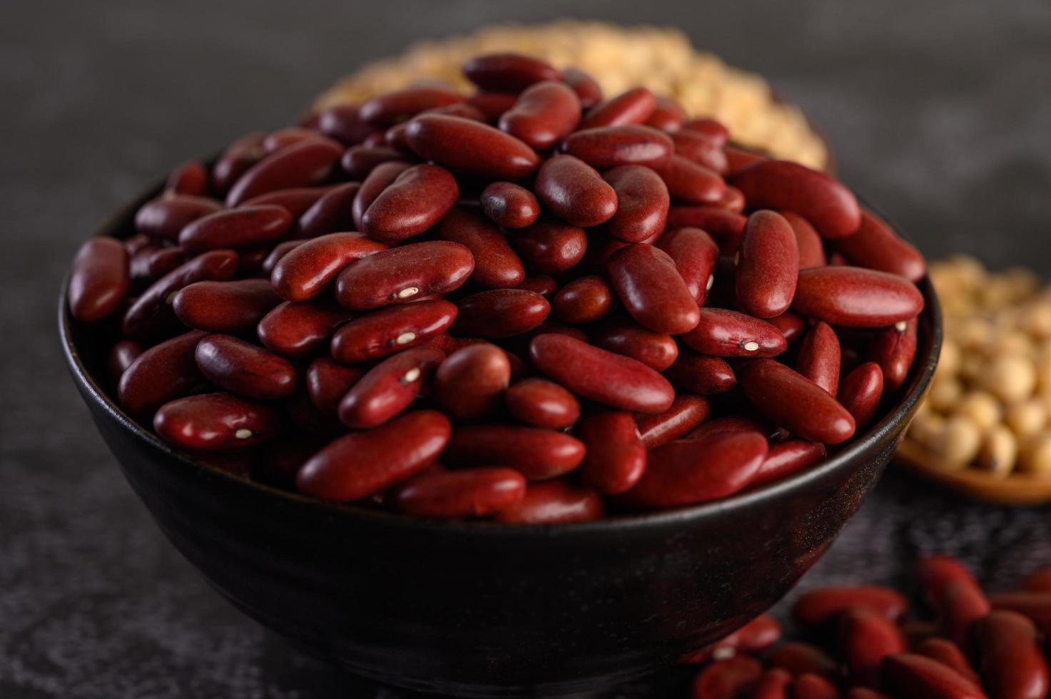 röda bönor i en träskål och brun sked foto