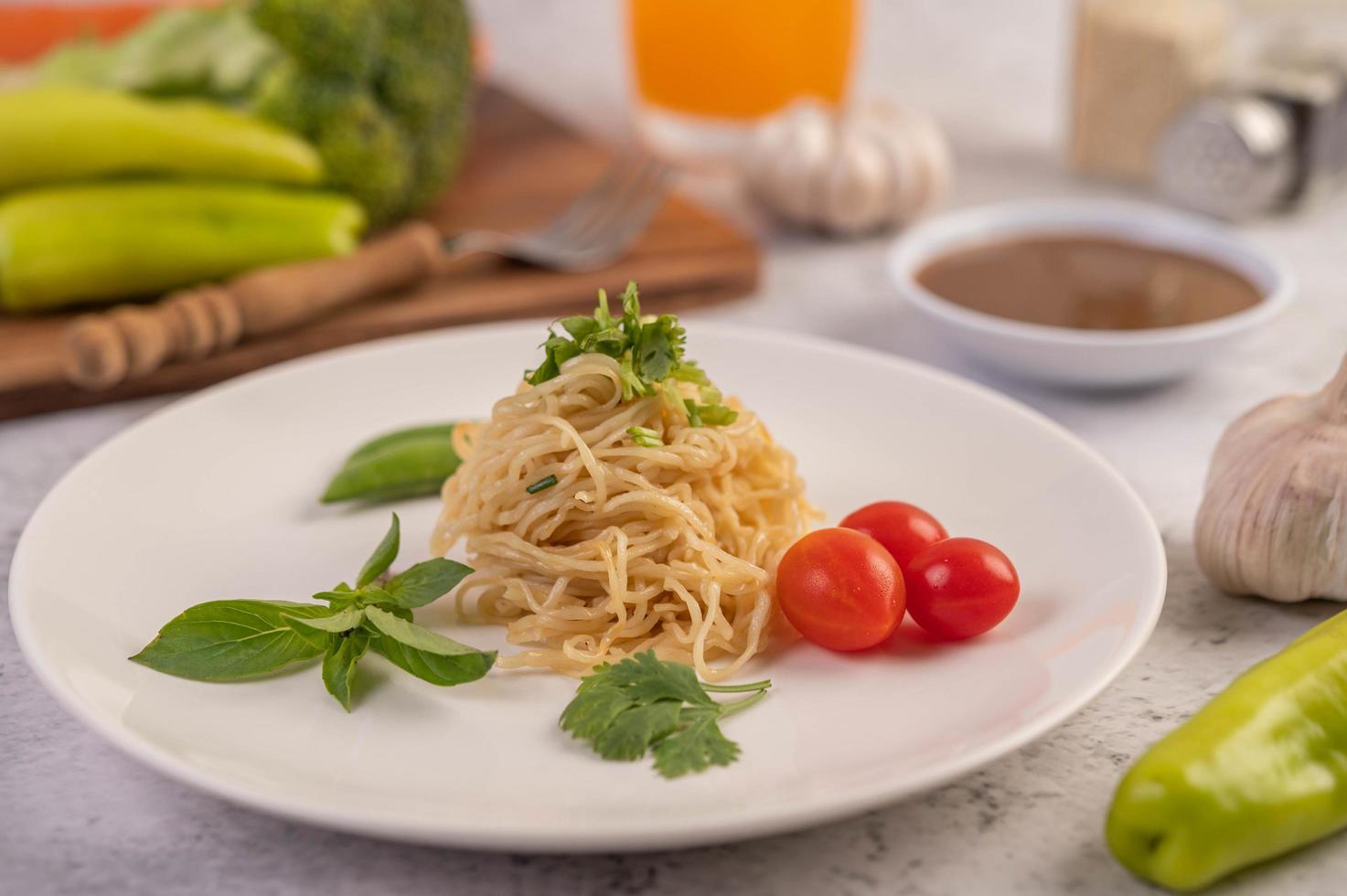 spagetti med tomater, koriander och basilika foto