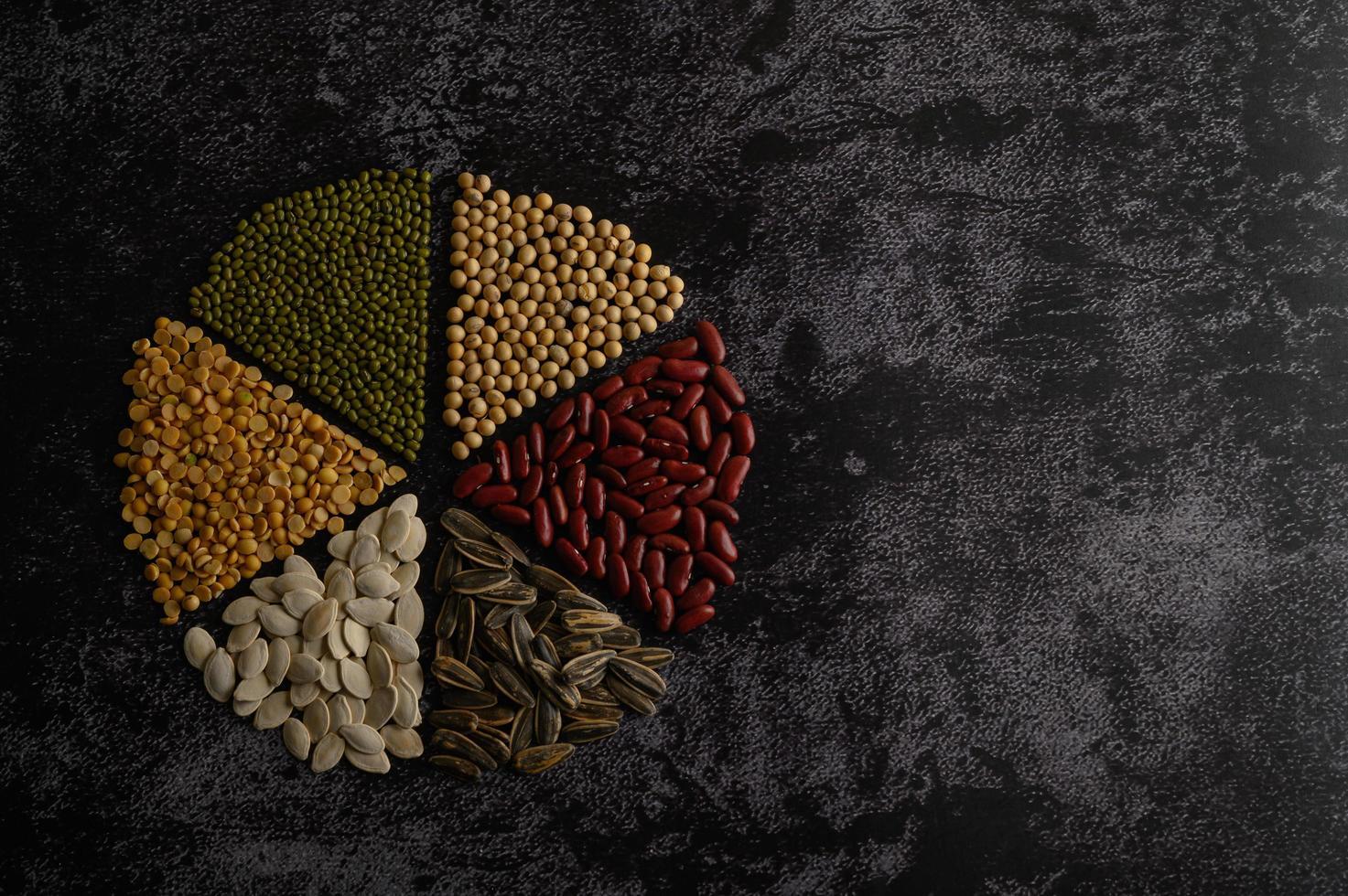 baljväxter ordnade i en cirkel på en svart cementyta foto