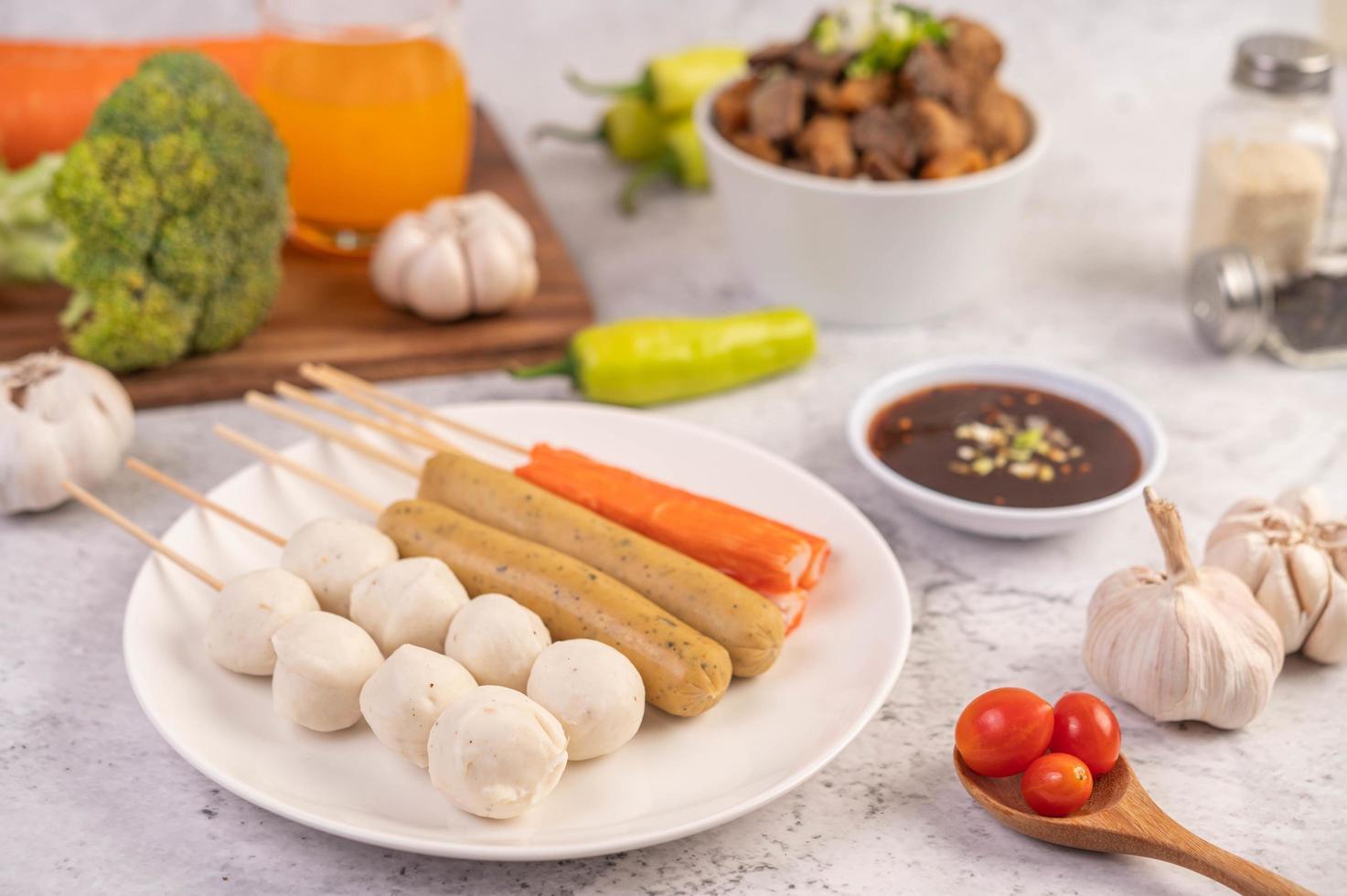 fläskköttbullar och spett med korv och grönsaker foto