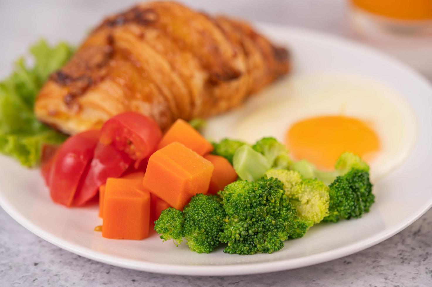 färsk äggcroissant och grönsaksfrukost foto