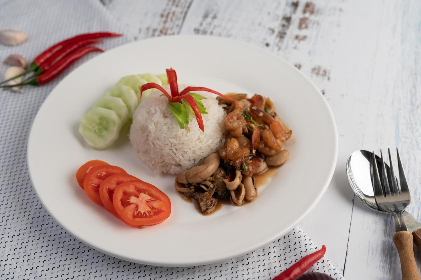 ris toppat med stekt basilika med bläckfisk och räkor foto