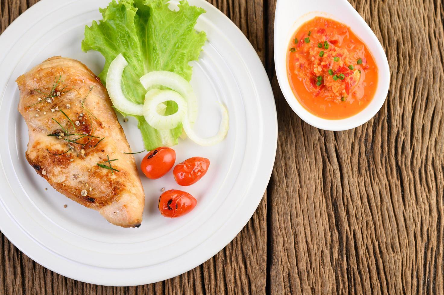grillad kyckling på ett träbord med tomater, sallad, lök och chilisås foto