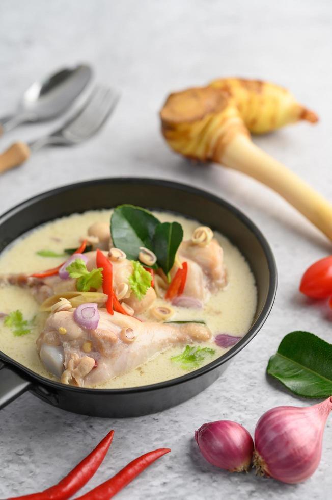 tom kha kai soppa med kaffir lime blad, citrongräs, rödlök, galangal och chili foto