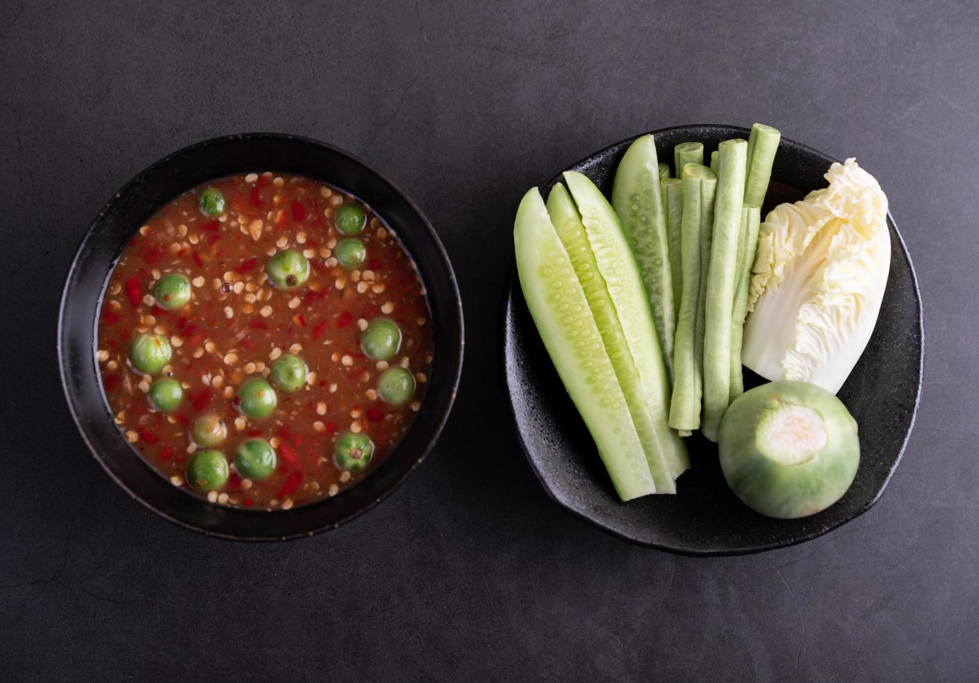 räkor-pastasås i en svart skål med gurka, bönor och thailändsk aubergine foto