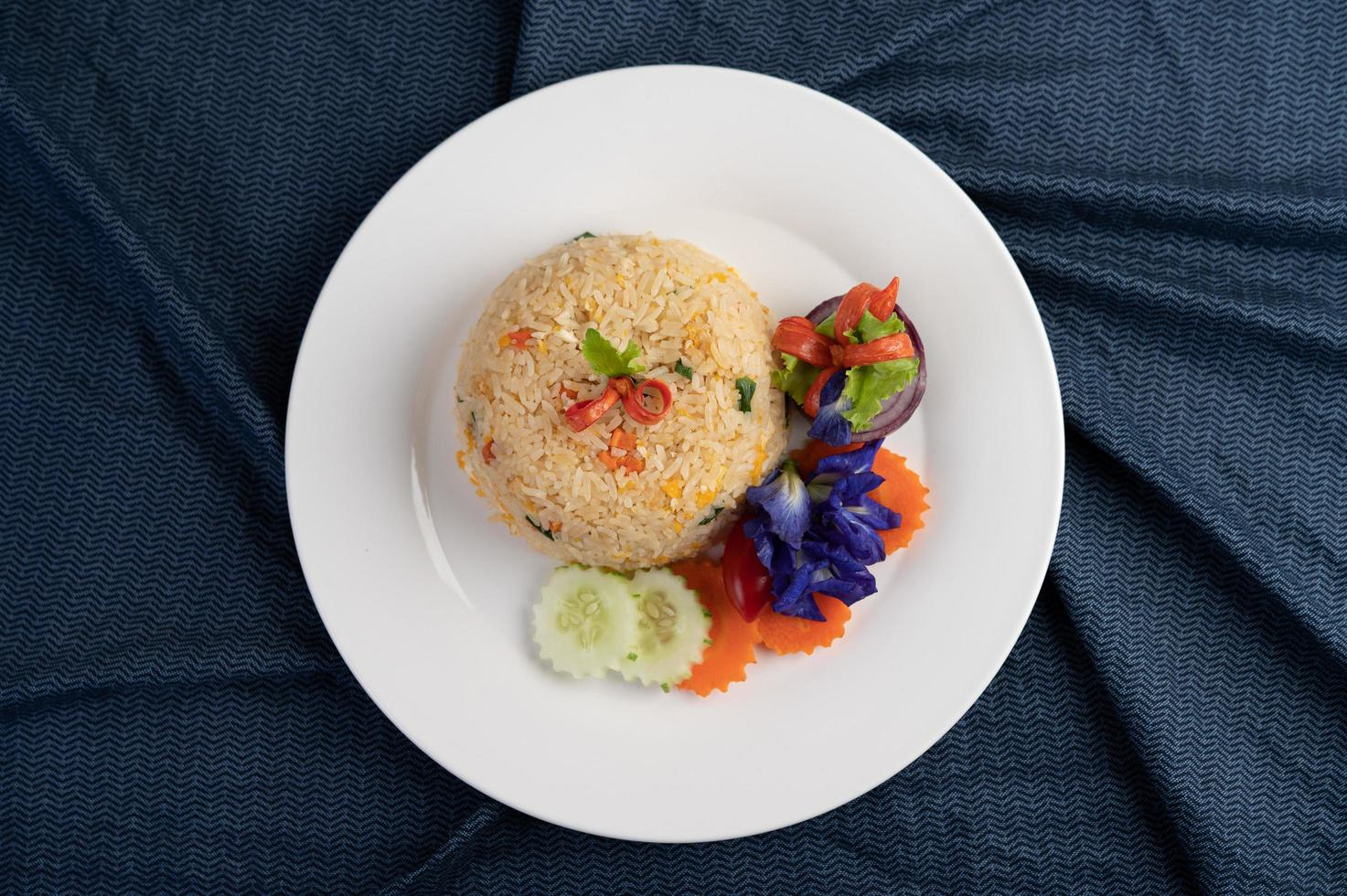 äggstekt ris på en vit platta med skrynkligt tyg foto
