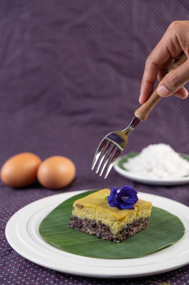 en gaffel sträcker sig efter svart klibbigt ris efterrätt foto