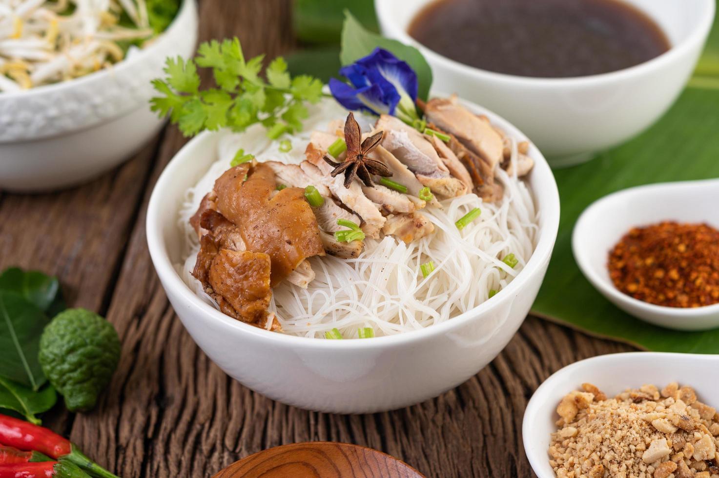 kycklingnudlar i en skål med thailändska sidorätter foto