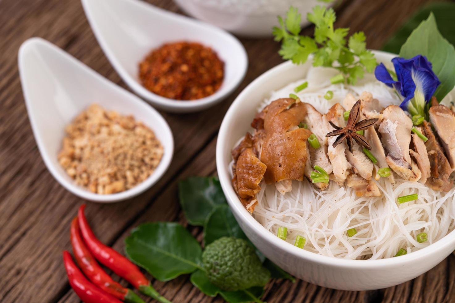 kyckling och nudlar i en skål med sidrätter foto