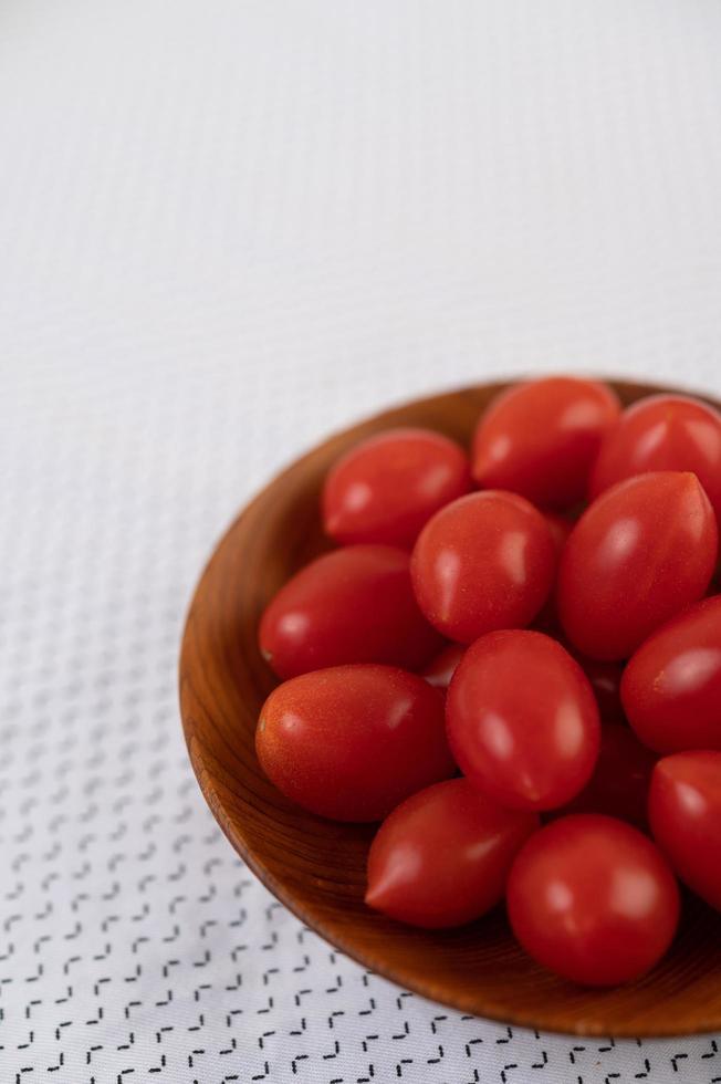 tomater i en träkopp på en vit trasa foto