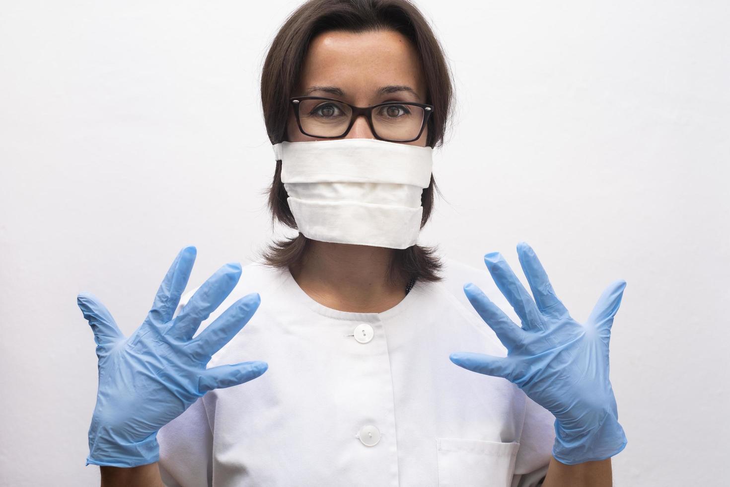 sjuksköterska som bär en mask och blå handskar på sjukhuset foto