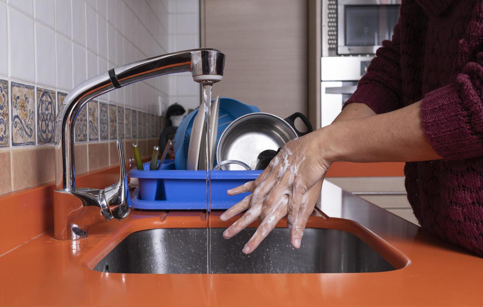 kvinna som tvättar händerna i köket foto