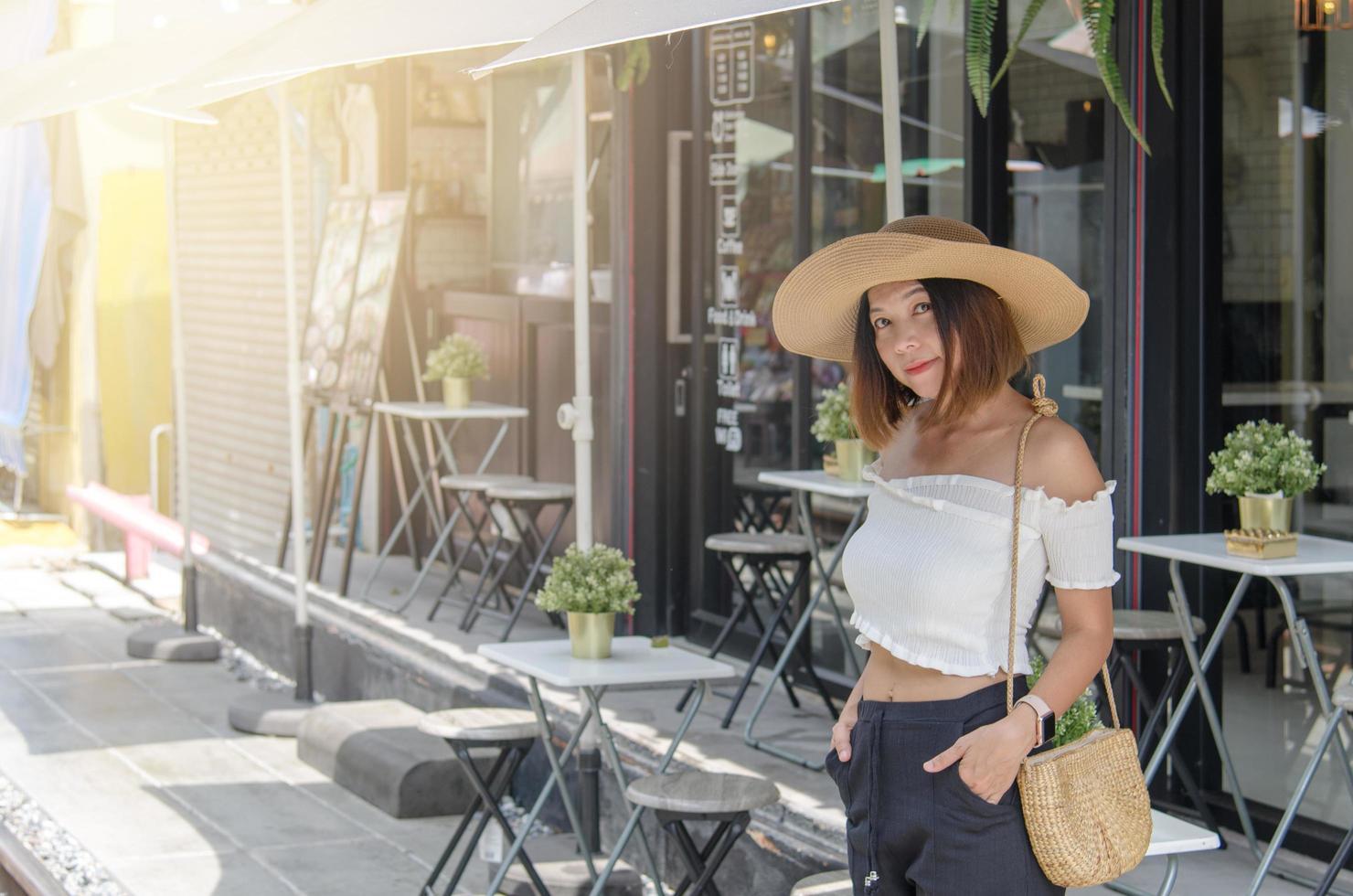 asiatisk kvinna som poserar utanför ett kafé foto