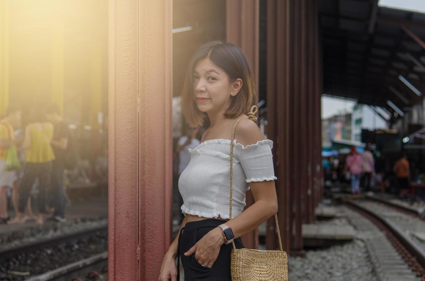 asiatisk kvinna som poserar på tågspåren foto