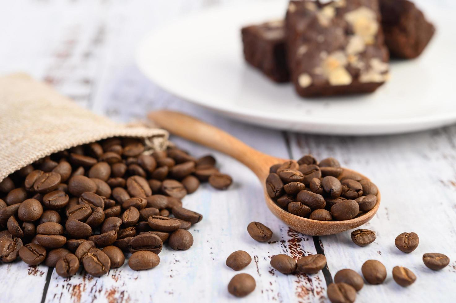 kaffebönor i en träsked och hampasäckar på ett vitt träbord foto