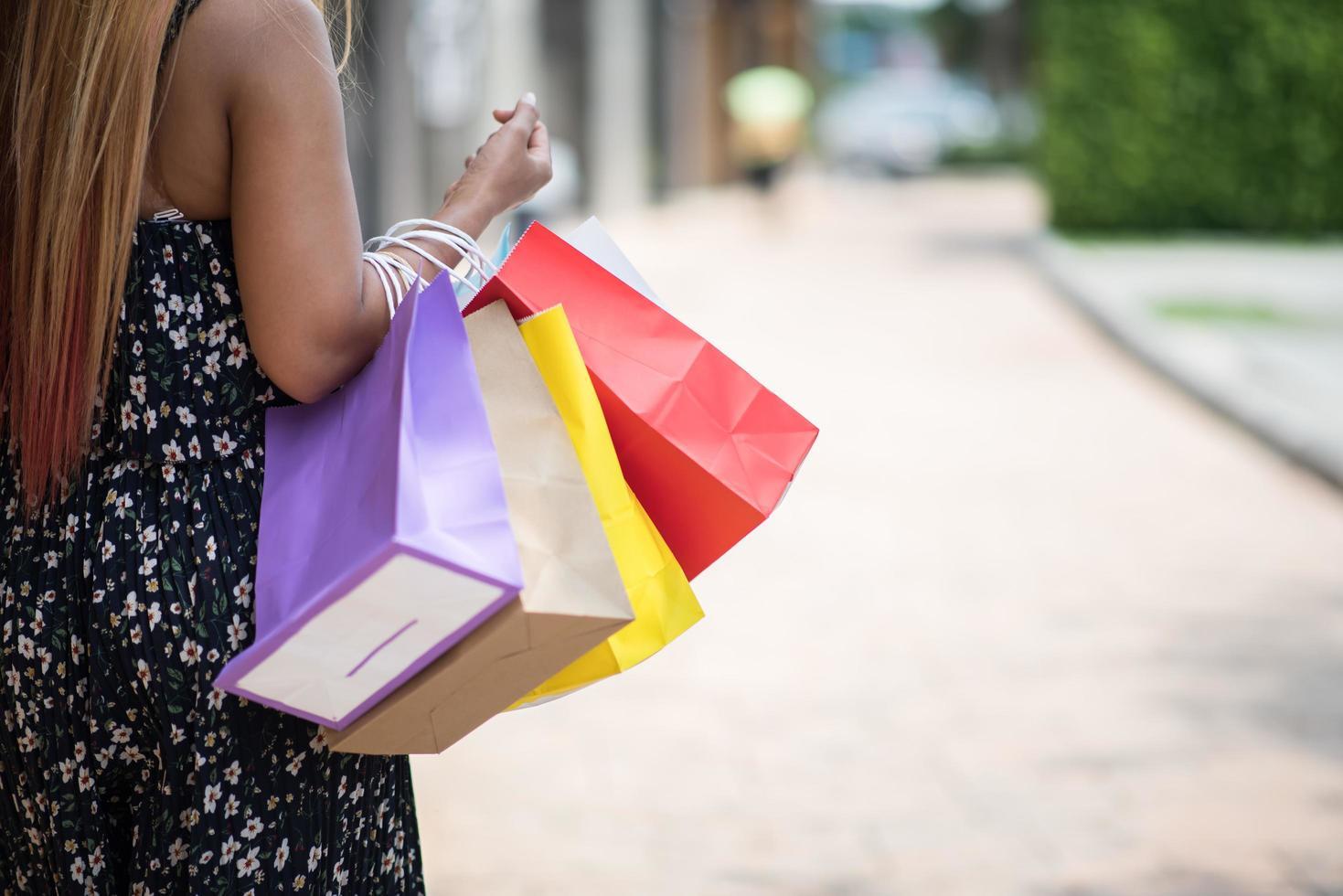 porträtt av en ung lycklig le kvinna med shoppingkassar i staden foto