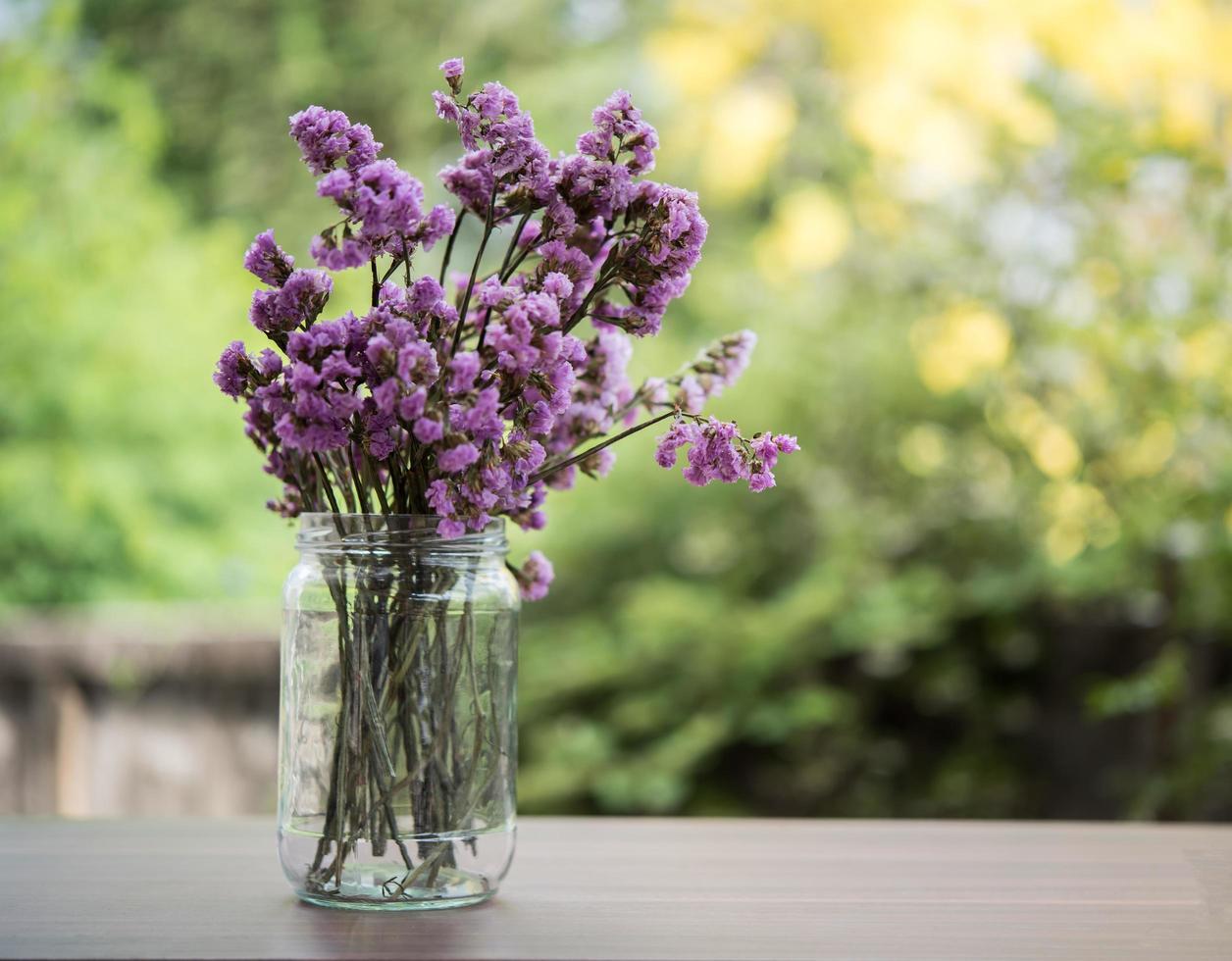 vackra blommor i en glasvas på träbord foto
