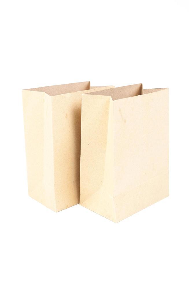 två bruna papperspåsar på vit bakgrund foto