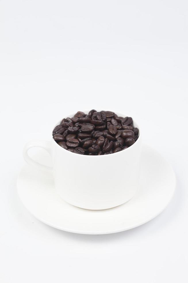 kopp med kaffebönor på vit bakgrund foto