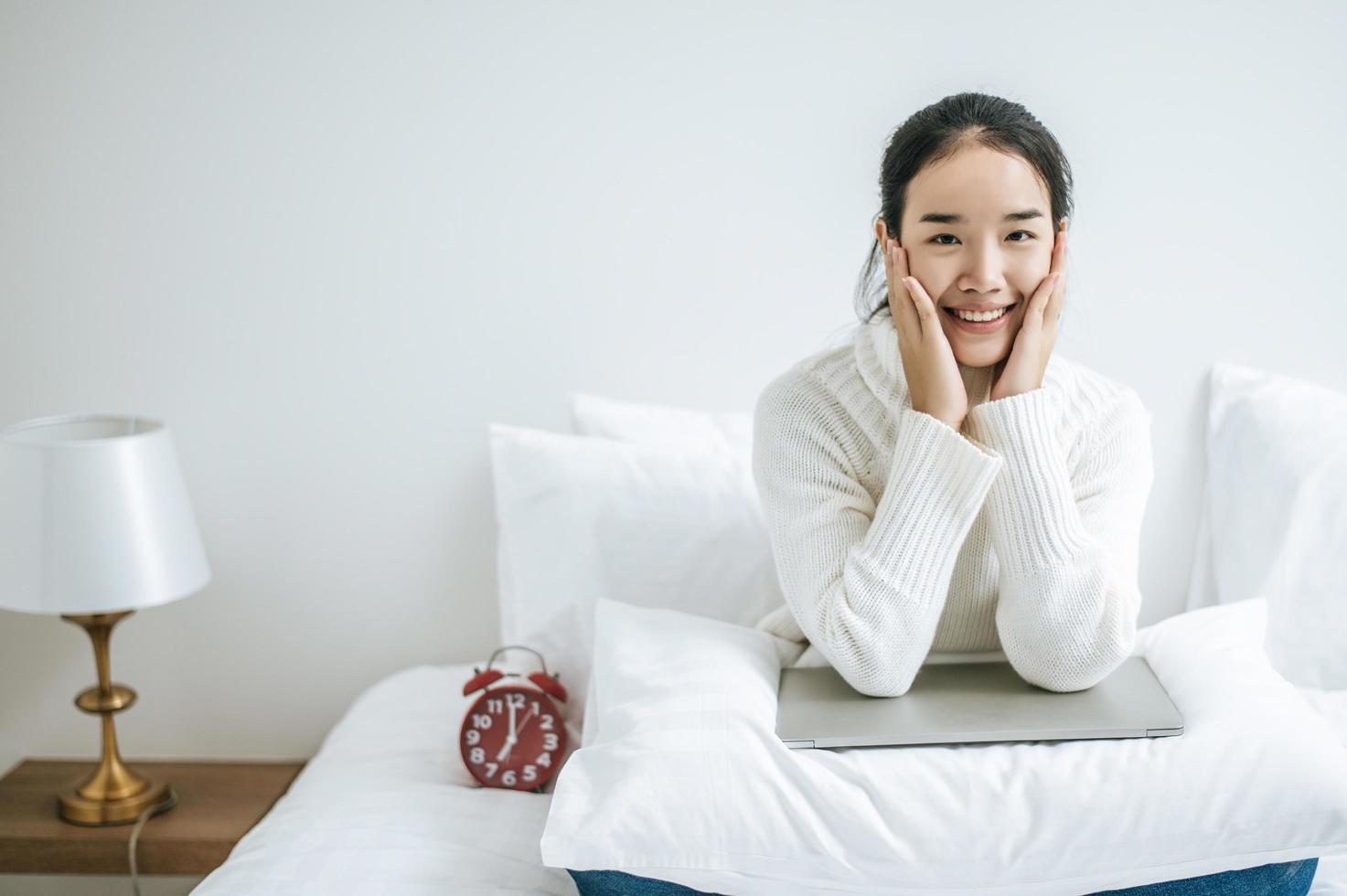 ung kvinna som sitter på sin säng med händer som rör kinderna foto