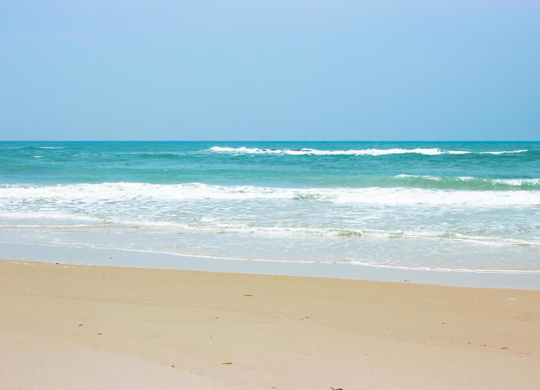havsvågor på stranden med klarblå himmel foto