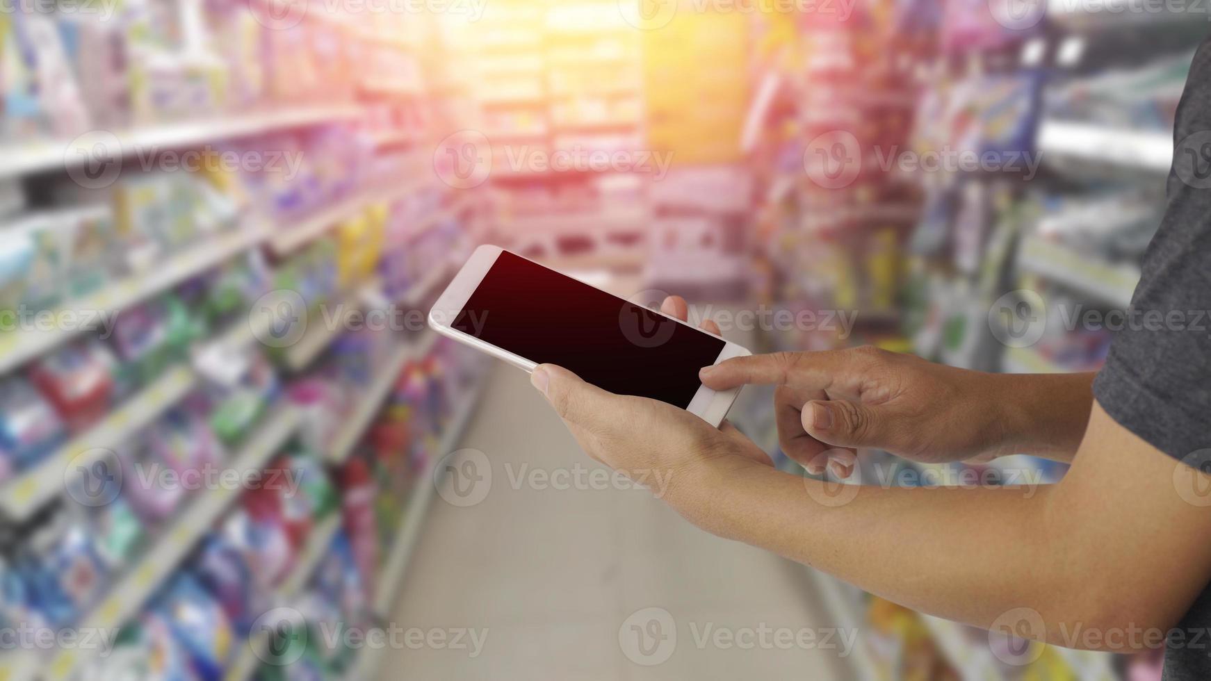 händer med blank skärm mobiltelefon med suddig bakgrund i varuhuset foto